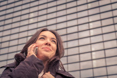 Young beautiful girl talking on phone in the city streets Stock Photography