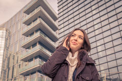 Young beautiful girl talking on phone in the city streets Royalty Free Stock Image