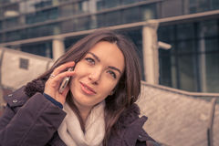 Young beautiful girl talking on phone in the city streets Royalty Free Stock Photo