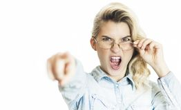 Young beautiful girl teacher in glasses emotionally reeks and shouts with a finger. Concept is evil doctor royalty free stock images