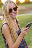 Young beautiful girl texting with her phone. Royalty Free Stock Photos