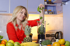 Young beautiful girl throwing baby spinach into the blender, making healthy smoothie Royalty Free Stock Image