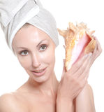 Young beautiful girl in a towel on the head with a big sea shell Stock Photos