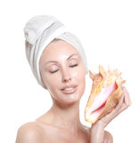 Young beautiful girl in a towel on the head with a big sea shell Royalty Free Stock Photos