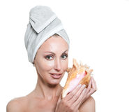The young beautiful girl in a towel on the head with a big sea shell Stock Photo