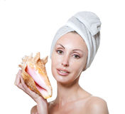 The young beautiful girl in a towel on the head with a big sea shell Stock Image