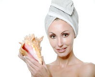 The young beautiful girl in a towel on the head with a big sea shell Royalty Free Stock Images