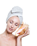 The young beautiful girl in a towel on the head with a big sea shell Stock Photos
