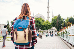 Young beautiful girl traveler with a backpack looking at a blue mosque - a famous tourist attraction of Istanbul. Travel