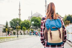 Young beautiful girl traveler with a backpack looking at a blue mosque - a famous tourist attraction of Istanbul. Travel Stock Photography