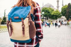 Young beautiful girl traveler with a backpack looking at a blue mosque - a famous tourist attraction of Istanbul. Travel Stock Images