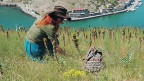 Beautiful red-haired girl in a cowboy hat walks through the mountains by the sea. Young beautiful girl traveler in a cowboy hat walks and collects medicinal stock footage