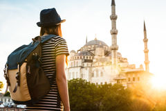 Young beautiful girl traveler in a hat with a backpack looking at a blue mosque - a famous tourist attraction of Royalty Free Stock Images