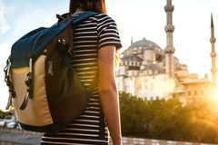 Young beautiful girl traveler in a hat with a backpack looking at a blue mosque - a famous tourist attraction of Royalty Free Stock Photo