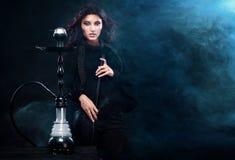 Young, beautiful woman in the night club or bar smoke a hookah. The pleasure of smoking. Sexy smoke. Stock Images