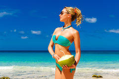 Young beautiful girl in the turquoise bikini is standing on the Stock Photo