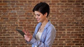 Young beautiful girl is typing message on her tablet, comunication concept, brick background.  stock footage