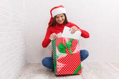 The girl unpacks a gift in a red bag stock photos