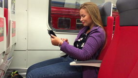 Young beautiful girl use a tablet computer sitting in a subway car.  stock footage