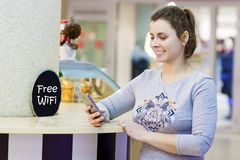 Young beautiful girl uses smartphone in free Wi Fi zone in shopping mall cafe. Attractive woman Wifi zone. Free wi-fi concept. Young beautiful girl uses royalty free stock photography