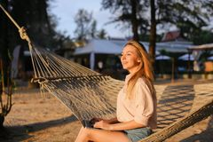 Young beautiful girl using laptop and sitting on sand in wicker hammock. royalty free stock photo