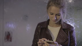 Young beautiful girl using a smartphone near the fountain stock footage