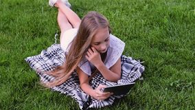 Happy girl using tablet pc lies on grass in the park stock video