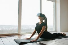 A young beautiful girl in virtual reality glasses makes yoga and aerobics remotely. Future technology concept. Modern Stock Photography