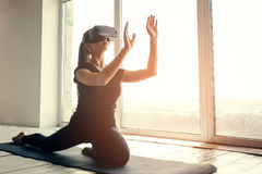 A young beautiful girl in virtual reality glasses makes yoga and aerobics remotely. Future technology concept. Modern. A young beautiful girl in virtual reality Royalty Free Stock Image