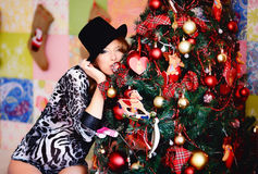 Young beautiful girl is waiting for the child on the eve of the. New year. She dressed the tree and tried on her hat Stock Image