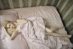 Young beautiful girl wakes up in the morning in a bed Stock Photo