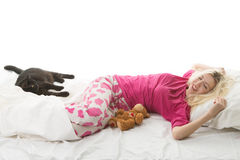Girl wakes up. Young beautiful girl wakes up. Next to them are a cat and a toy bear Stock Photos