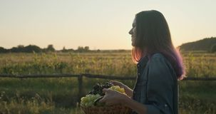 Young beautiful girl walking with a basket of grapes stock video