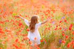 Young beautiful girl walking and dancing through a poppy field, Royalty Free Stock Photography