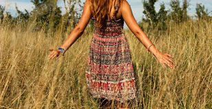 Young beautiful girl walking in the field and runs hand through the high dry grass at summertime Stock Image