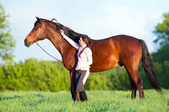 Young beautiful girl walking with a horse in the field. Young beautiful girl walking with a bay horse in the field in spring Royalty Free Stock Photos