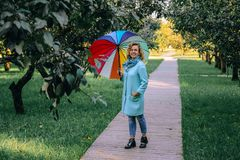 Young beautiful girl walks in the autumn park with a colorful umbrella stock photos