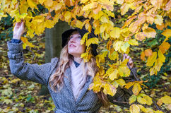 The young beautiful girl walks in the autumn park among yellow leaves in a coat on a sunny day Stock Photo
