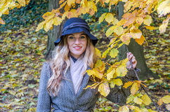 The young beautiful girl walks in the autumn park among yellow leaves in a coat on a sunny day Stock Photography