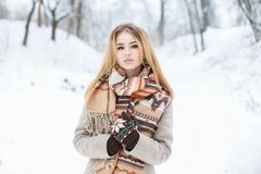 Young beautiful girl walks in winter park on vacation Royalty Free Stock Image