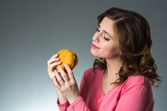 Young beautiful girl wants but can not eat fast food sandwich, s Royalty Free Stock Images