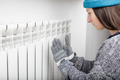 Young beautiful girl warms hands near a radiator. Dressed in gloves, a sweater and a hat Royalty Free Stock Photo