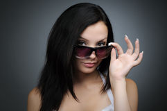 Young beautiful girl in wayfarer style glasses. On black background Royalty Free Stock Image