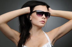 Young beautiful girl in wayfarer style glasses. On black background Stock Photography
