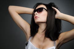 Young beautiful girl in wayfarer style glasses. On black background Royalty Free Stock Photo
