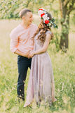 Young beautiful girl wearing flower wreath with her boyfriend holding hands in the spring garden Stock Photography