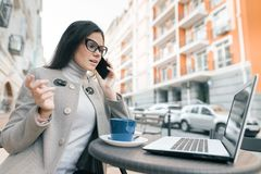 Young beautiful girl wearing glasses in warm coat sitting in outdoor cafe with laptop with cup of hot drink, talking on mobile stock photos