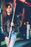 Young beautiful girl wearing leather jacket in a billiard club, with cue stick preparing for the game.  Royalty Free Stock Images