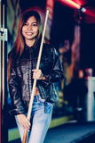 Young beautiful girl wearing leather jacket in a billiard club, with cue stick preparing for the game Stock Photos