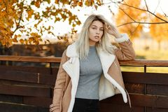 A young beautiful girl is wearing a stylish demi-season jacket. A gray sweater is standing in the forest with bright yellow leaves near a wooden wall. A woman stock photos